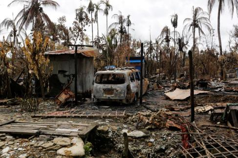 A car is seen near a house that was burnt down during the last days violence in Maungdaw